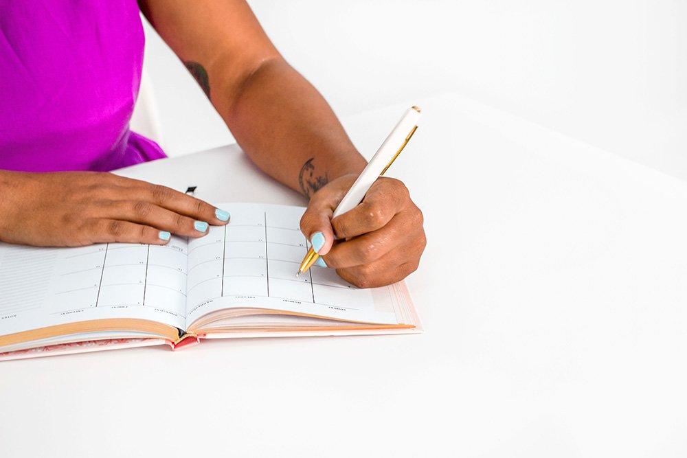 african american woman writing social media into a content calendar